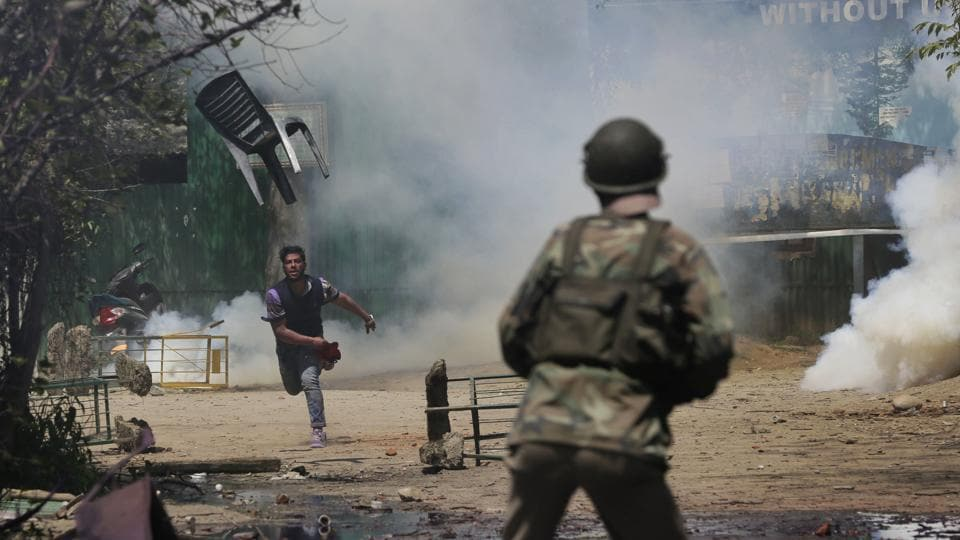 A student throws a chair towards police officers during a clash in Srinagar. Hundreds of college students took to the streets to protest a police raid in a college in southern Pulwama town over the weekend, in which at least 50 students were injured.