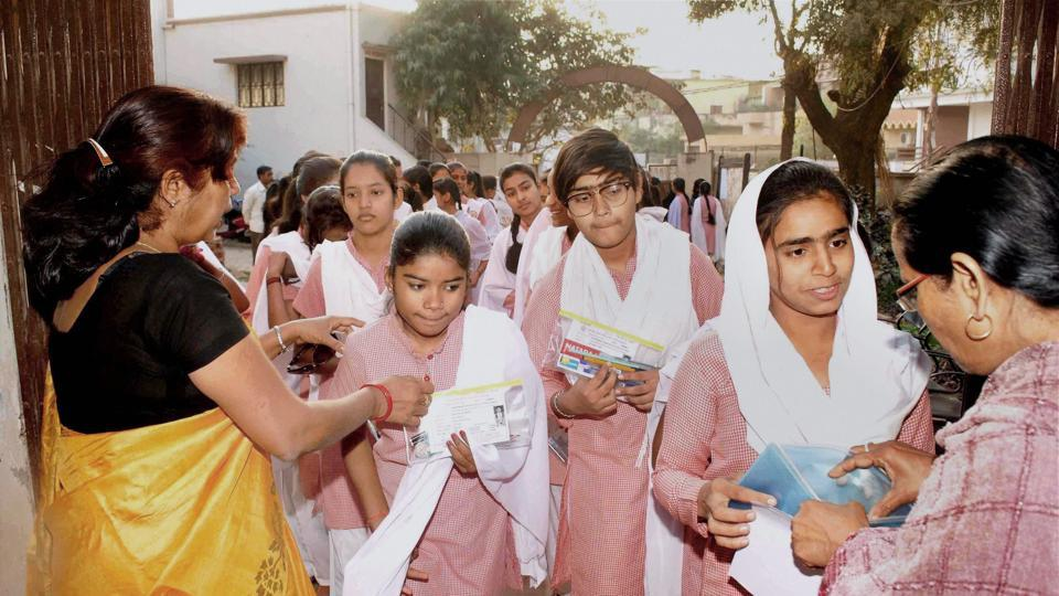 Teachers check students as they arrive to give their high school exam in Allahabad.