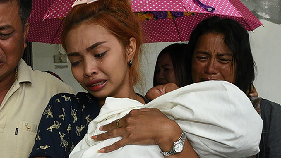 Jiranuch Trirat carries the body of her 11-month-old daughter as she is surrounded by relatives and friends outside the morgue in Phuket.