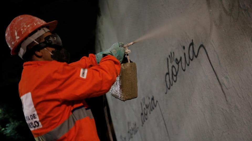 A municipal worker removes the writing 'doria'  in reference to Sao Paulo's mayor Joao Doria, tagged by a Brazilian artist, known as Iaco, on Avenida 23 de Maio. (Nacho Doce  / REUTERS)