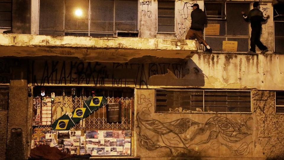 A homeless man (L) sleeps as 'pichadores', graffiti artists who tag buildings and landmarks . (Nacho Doce  / REUTERS)