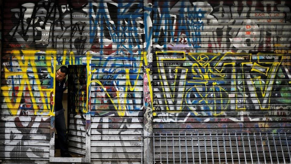 A man looks out of a door of his shop tagged by 'pichadores', graffiti . (Nacho Doce  / REUTERS)