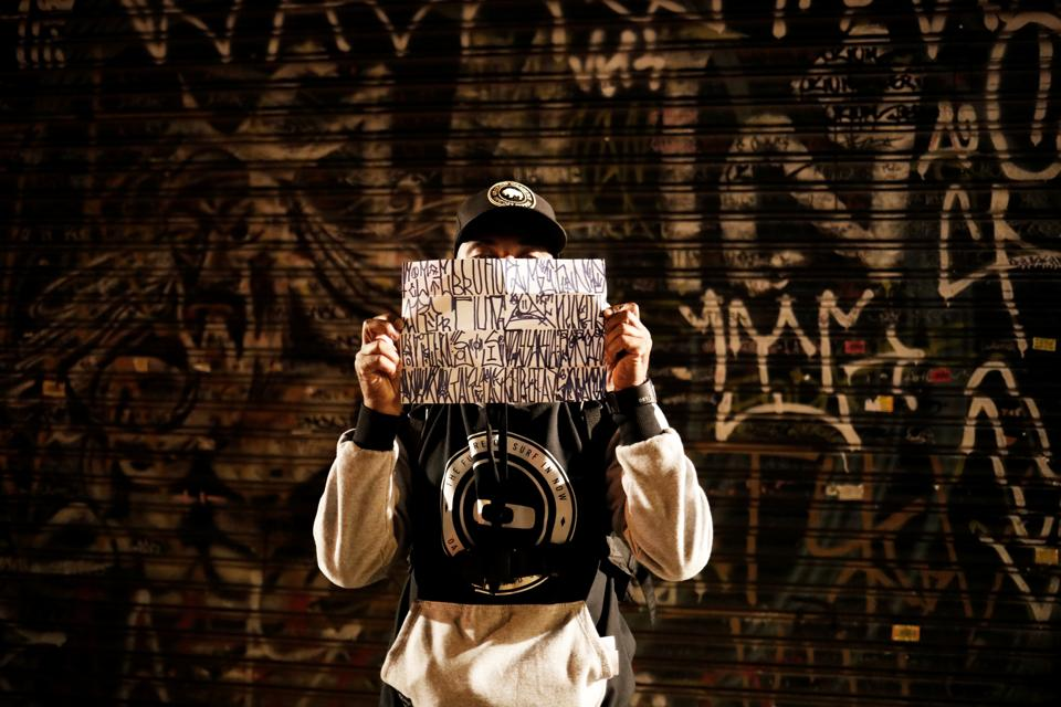 A 'pichador', a graffiti artist who tags buildings and landmarks with angular, runic fonts, holds a paper with personal signatures, called  'pichacao' during the