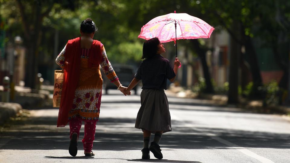 A girl covers herself with an umbrella against a harsh sun while returning from school. (Ravi Choudhary/HT PHOTO)