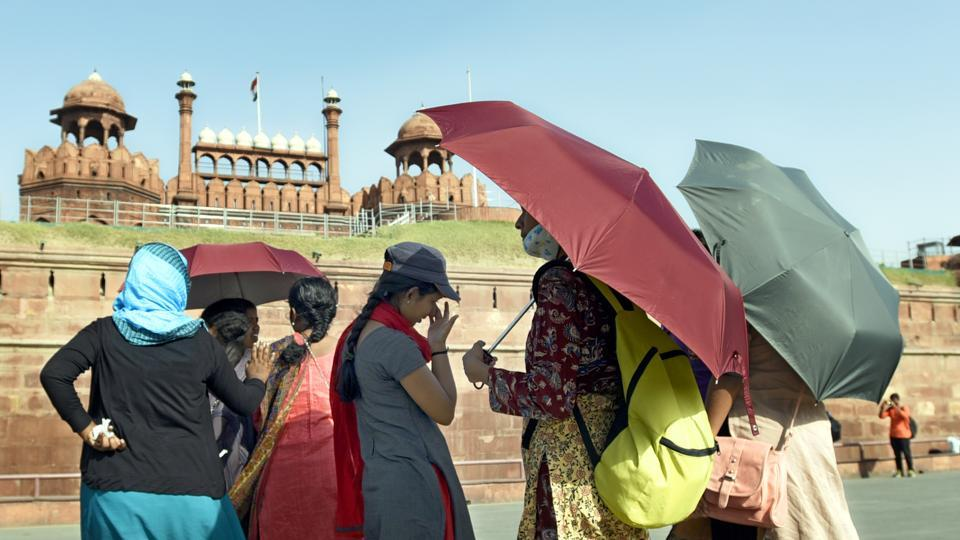 Visitors to the Red Fort cover themselves to protect from the heat. (Sonu Mehta/HT PHOTO)