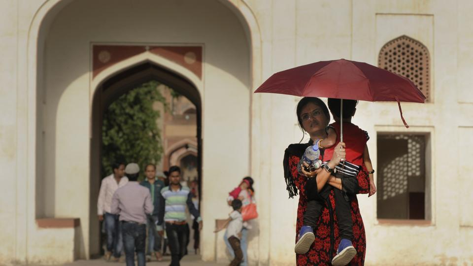 A mother holds her child under an umbrella to protect themselves from the scorching sun at Humayun's Tomb. Hot weather conditions continued to prevail in Delhi with maximum temperatures exceeding 40 degrees Celsius with intermittent showers and clouds. (Burhaan Kinu/HT PHOTO)