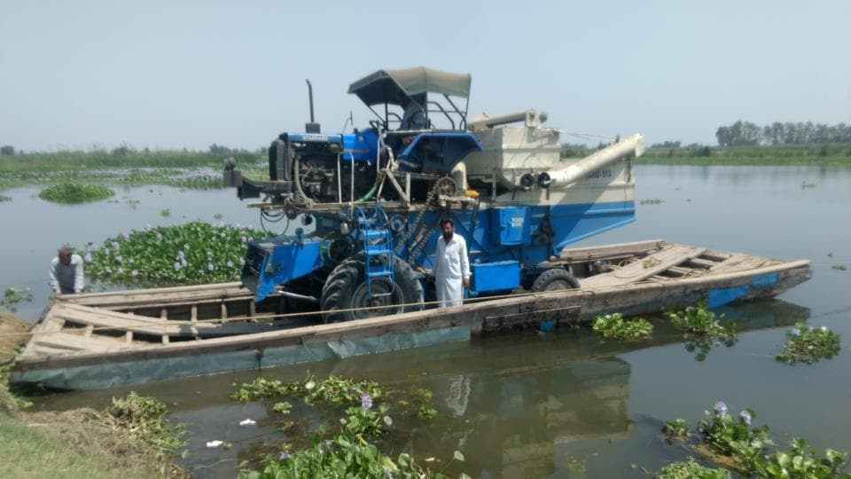 Farmers transporting a combine harvester on a non-motorised boat to harvest wheat crop across the Sutlej river.