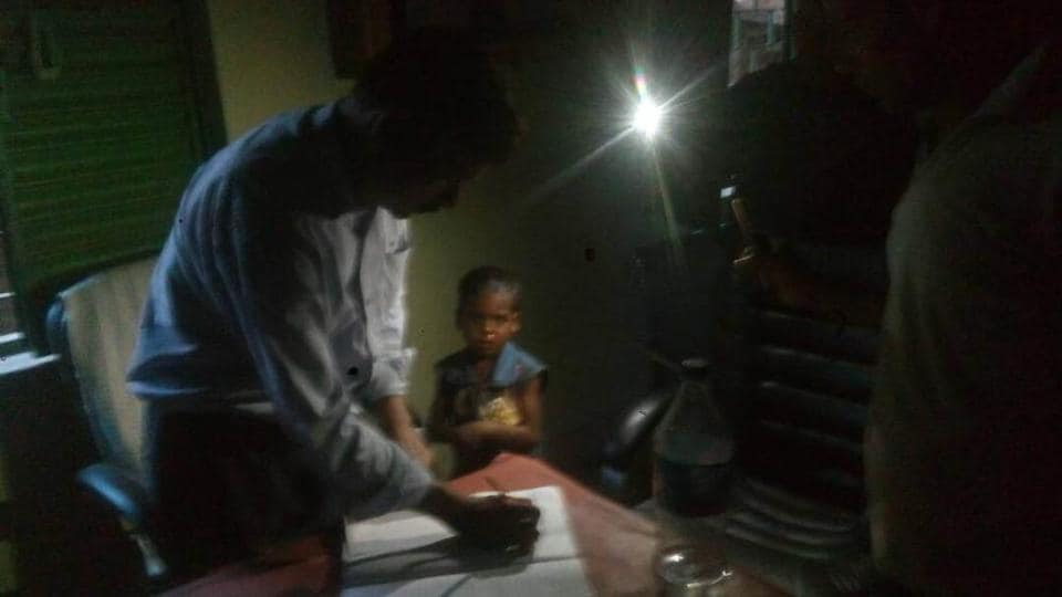 A doctor works under a mobile flashlight in Balumath in Jharkhand.
