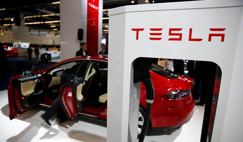 A Tesla model S car with an electric vehicle charging station is displayed during a media preview day at the Frankfurt Motor Show.