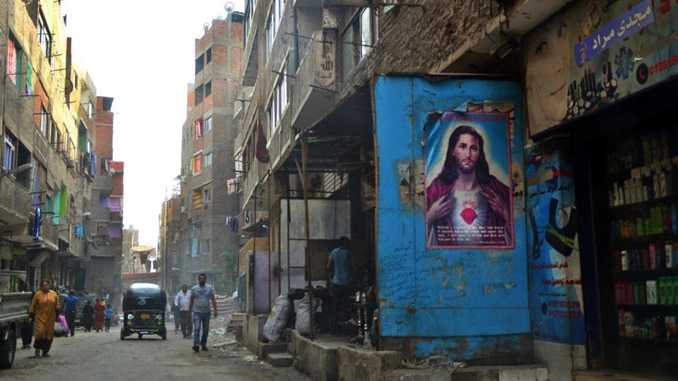 People walk past a poster bearing a portrait of Jesus Christ in the Zabalin area a day ahead of the visit of Pope Francis to the capital Cairo. (MOHAMED EL-SHAHED/AFP)