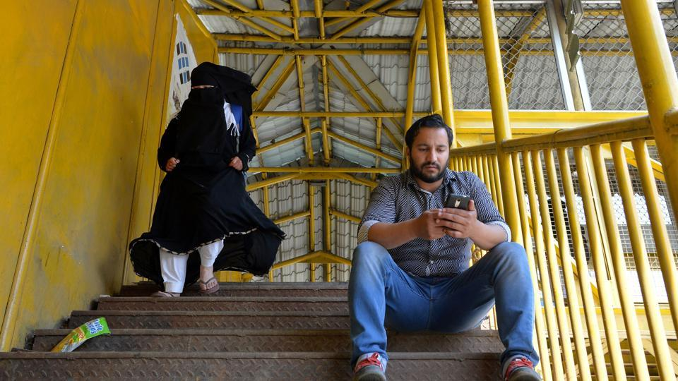 A Kashmiri man browses the internet on his mobile phone on a footbridge in Srinagar.