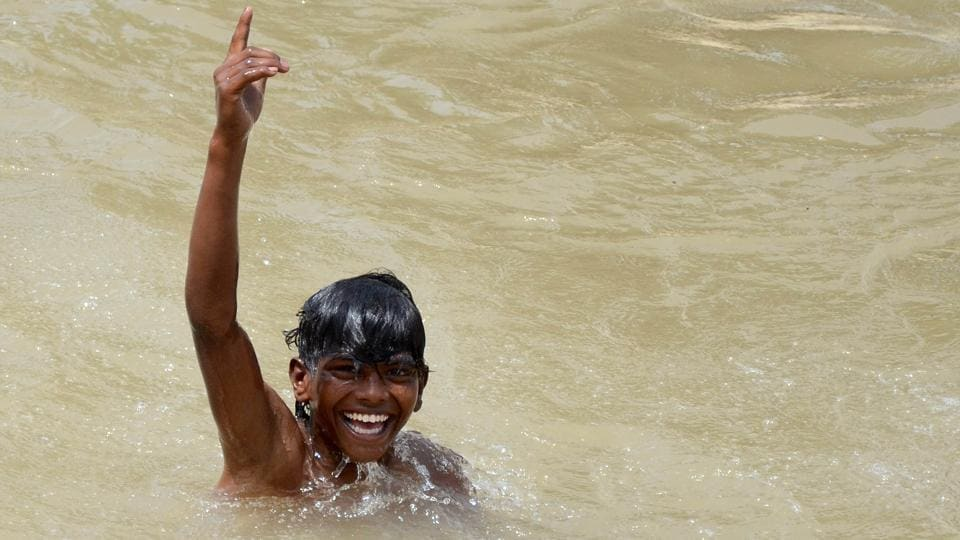TAKE A DIP: A boy is all smiles as he bathes in the Sidhwan Canal in Ludhiana. (Gurminder Singh/HT )