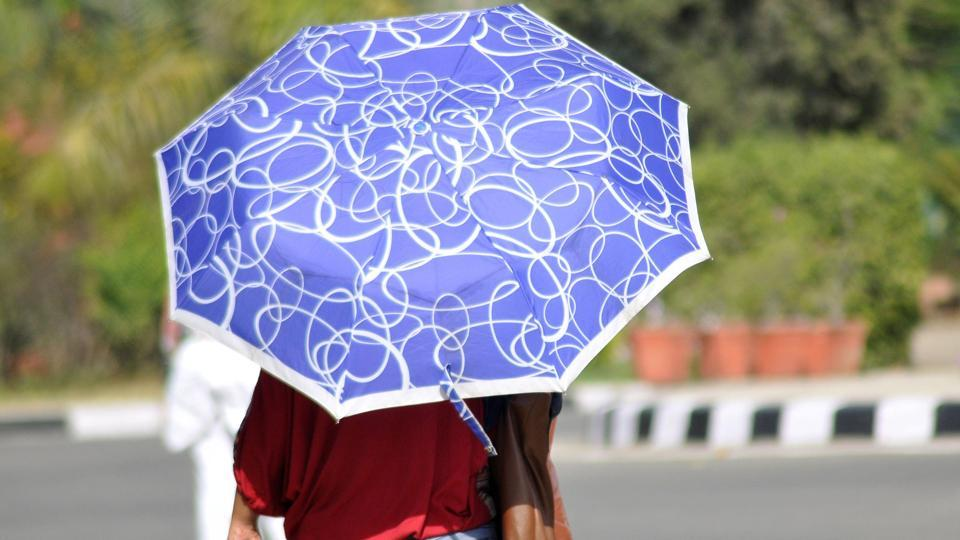 UNDER MY UMBRELLA: A Ludhiana girl uses the good, old umbrella to protect herself. (Gurminder Singh/HT )
