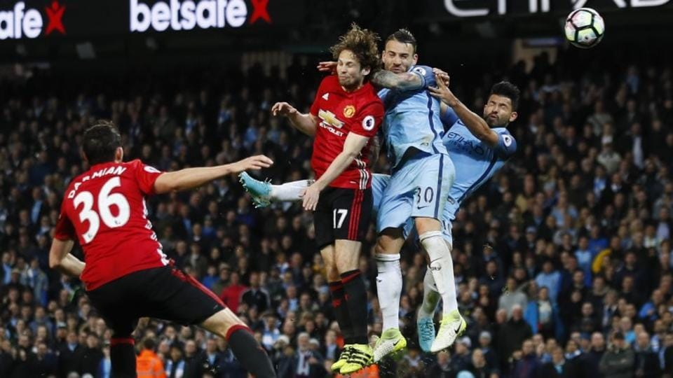 Manchester City F.C.'s Sergio Aguero (right) and Nicolas Otamendi attempt an header at goal with Manchester United F.C.'s Daley Blind trying to defend during their English Premier League match -- The Manchester Derby -- on Thursday.