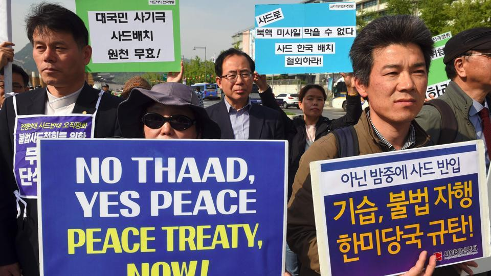 South Korean protesters hold placards during a rally against the deployment of the US Terminal High Altitude Area Defense (THAAD) system near the US embassy in Seoul on Friday.