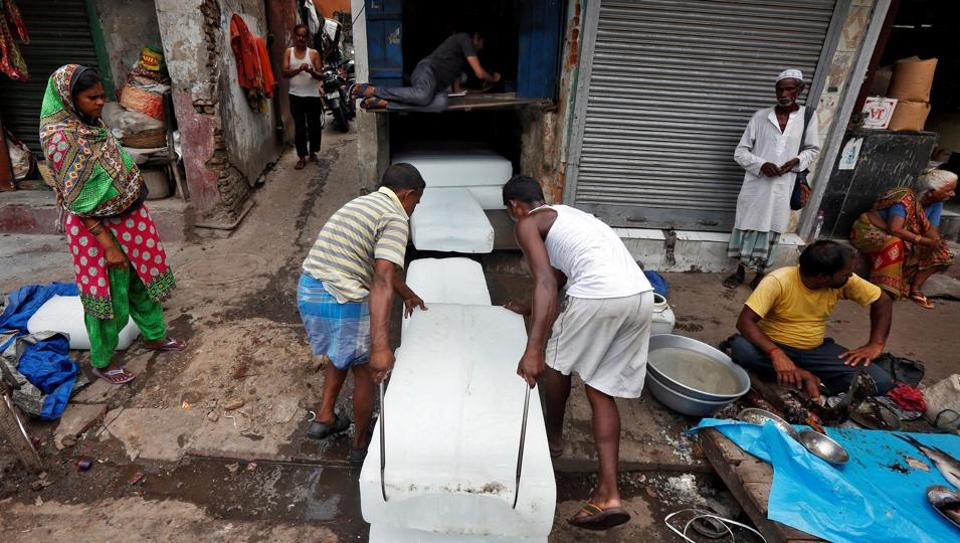 Workers stack blocks of ice on a hot summer day in Kolkata.