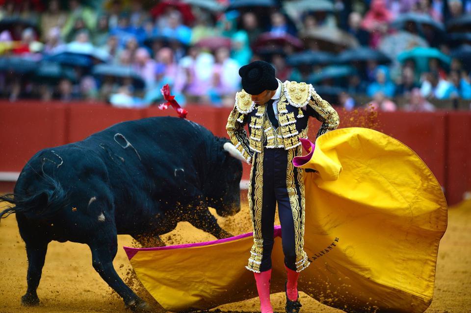Spanish matador Alejandro Talavante performs a pass with capote on a bull during a bullfight at the Maestranza bullring, in Sevilla. (CRISTINA QUICLER / AFP)