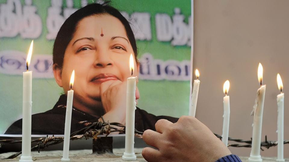 Jayalalithaa supporters light candles as they pay tribute after her death.