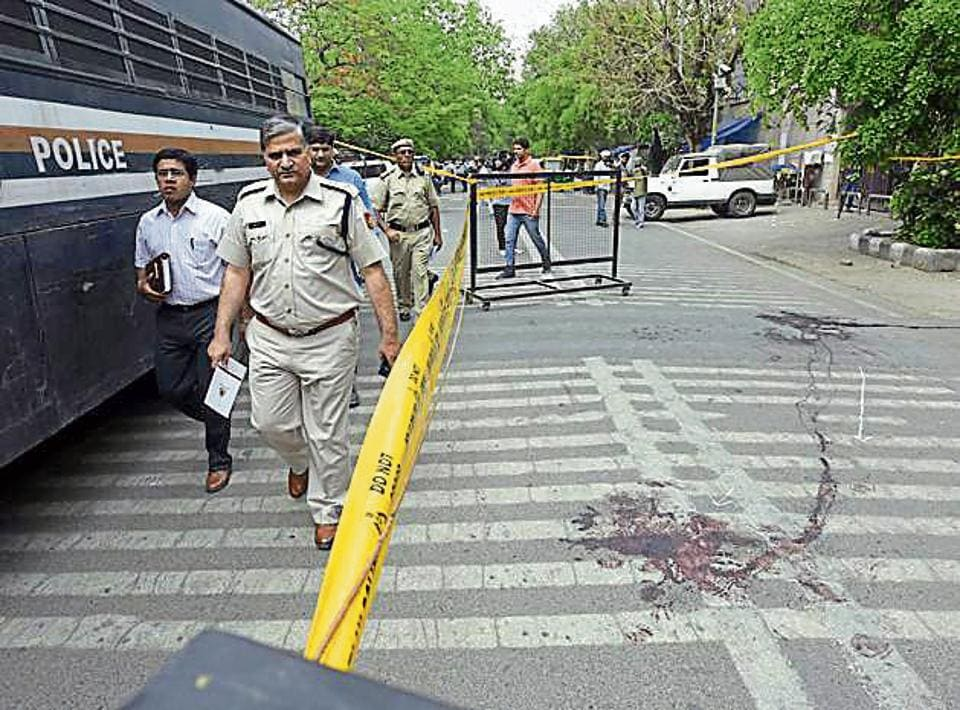 Deputy commissioner of police, Rishi Pal, and forensic experts collect samples outside Rohini court in New Delhi, India on Saturday.