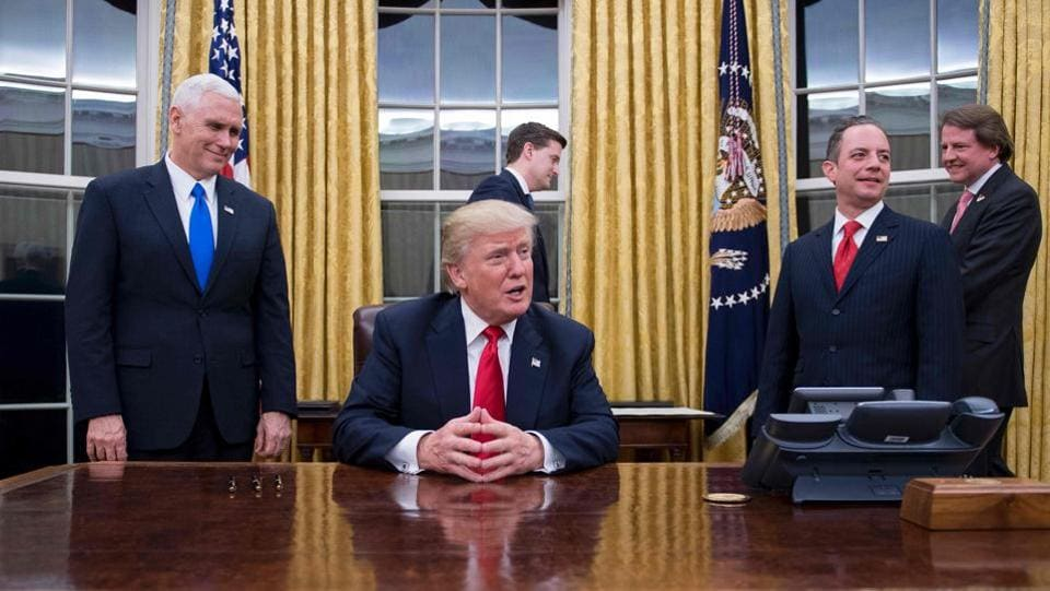 (FILES) US President Donald Trump (C) speaks to the press as he waits at his desk before signing conformations for General James Mattis as US Secretary of Defense and General John Kelly as US Secretary of Homeland Security, as Vice President Mike Pence (L) and White House Chief of Staff Reince Priebus (R) look on, in the Oval Office of the White House in Washington, DC, January 20, 2017.  (JIM WATSON / AFP)