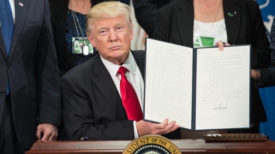 (FILES) US President Donald Trump signs an executive order to start the Mexico border wall project at the Department of Homeland Security facility in Washington, DC, on January 25, 2017.  (AFP)