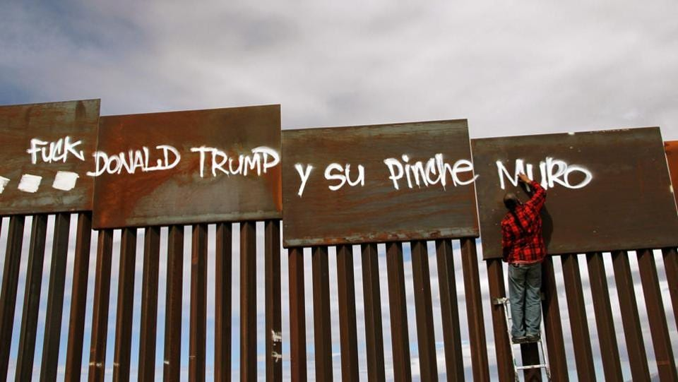 (FILES) An activist paints the wall between the United States and Mexico during a demonstration against US President Donald Trump on the border of Ciudad Juarez with Nuevo Mexico, Chihuahua State, Mexico on February 26, 2017.  (AFP)