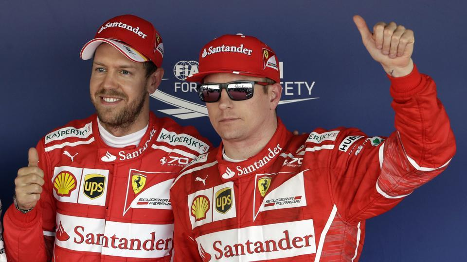 Ferrari drivers Sebastian Vettel (left) and Kimi Raikkonen (Finland) pose for photos after securing the pole and second spot respectively in qualifying for the Russian Grand Prix on Saturday.