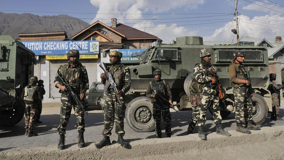 Paramilatary troopers stand guard near the site of a militant attack in Sempora area of Srinagar.