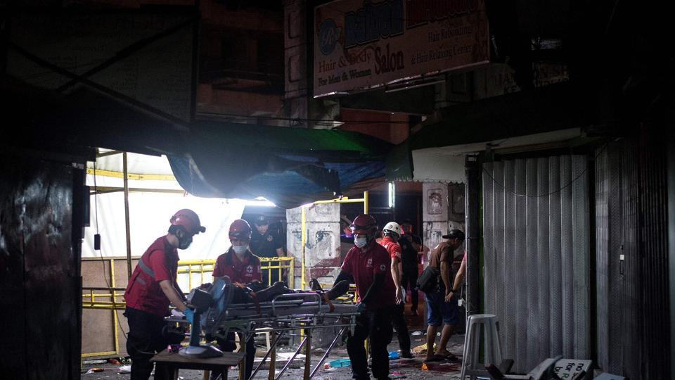 Rescue workers attend to a wounded man on a stretcher in an alley in Manila after a homemade pipe bomb exploded.