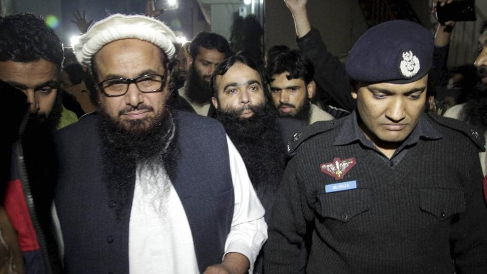 Hafiz Saeed (L) being escorted by a police official in Lahore, Pakistan.