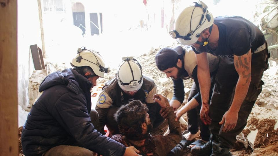 Members of the Syrian civil defence volunteers, also known as the White Helmets, remove a victim from the rubble of his house after an air strike by government forces early this month.