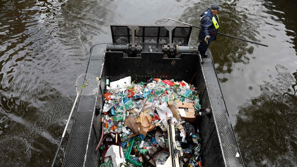 A worker cleans garbage with a boat in the canals of Amsterdam, on April 28, 2017, a day after Kings Day was celebrated. (Bas Czerwinski / AFP)