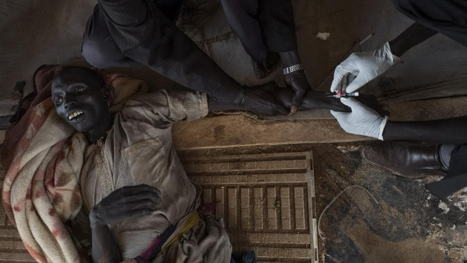 A patient with cholera is treated moments before his death at the temporary specialized hospital in Mingkaman, a camp for the Internally displaced people (IDPs) on April 26, 2017, in the Eastern Lakes States. Many of the displaced people have crosssed the Nile to reach the Mingkaman camp from neighbouring states. (AFP)