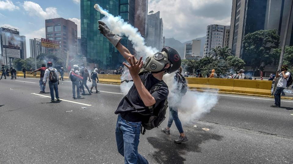 Opposition activists clash with riot police during a protest march in Caracas on April 26, 2017. Protesters in Venezuela plan a high-risk march against President Maduro Wednesday, sparking fears of fresh violence after demonstrations that have left 26 dead in the crisis-wracked country. (JUAN BARRETO / AFP)