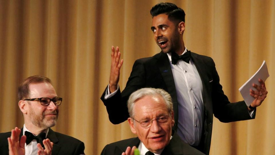 Hasan Minhaj (R) of Comedy Central walks past veteran Washington Post journalist Bob Woodward (C) and Reuters Editor-in-Chief Steve Adler (L) as he takes the lectern to perform at the White House Correspondents' Association dinner in Washington.