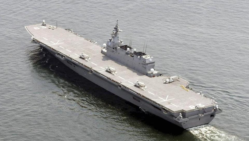Japan's helicopter carrier JS Izumo sails by a US supply ship at anchor in the waters off Yokosuka after the Japanese destroyer departed Yokosuka port, south of Tokyo on Monday.