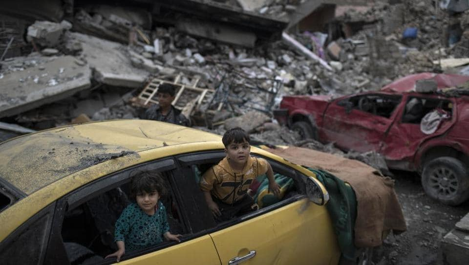 Children play inside a damaged car amid heavy destruction in a neighbourhood recently retaken by Iraqi security forces from Islamic State militants on the western side of Mosul.