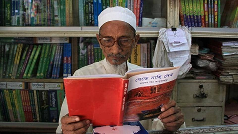 Bangladeshi novelist Kasem bin Abubakar poses for a photograph with a copy of one of his books at his book shop in Dhaka.