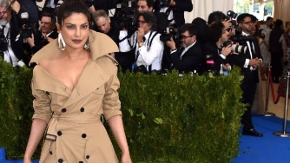 The Quantico star teamed up the trench coat gown with black boots and sculptural earrings.