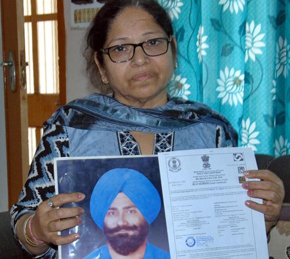 Paramjit Kaur, wife Manjit Singh Sethi showing his photo and death certificate at her home in Amritsar.