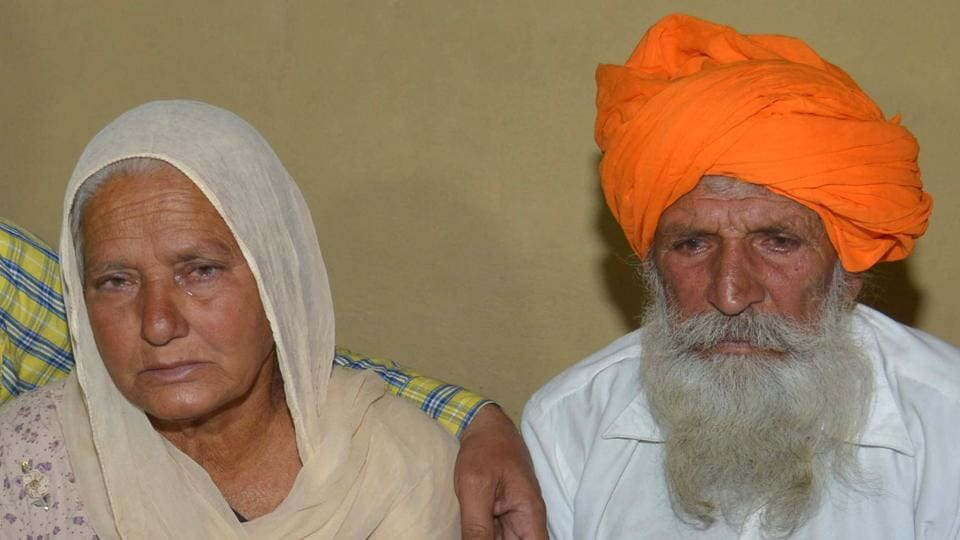 Udham Singh (R) and his wife Gurinder Kaur (L), father and mother of Indian Army soldier Paramjeet Singh cry as they hold a picture of their son at their residence AT Vein Pein village, some 45 km from Amritsar, on May 1, 2017.