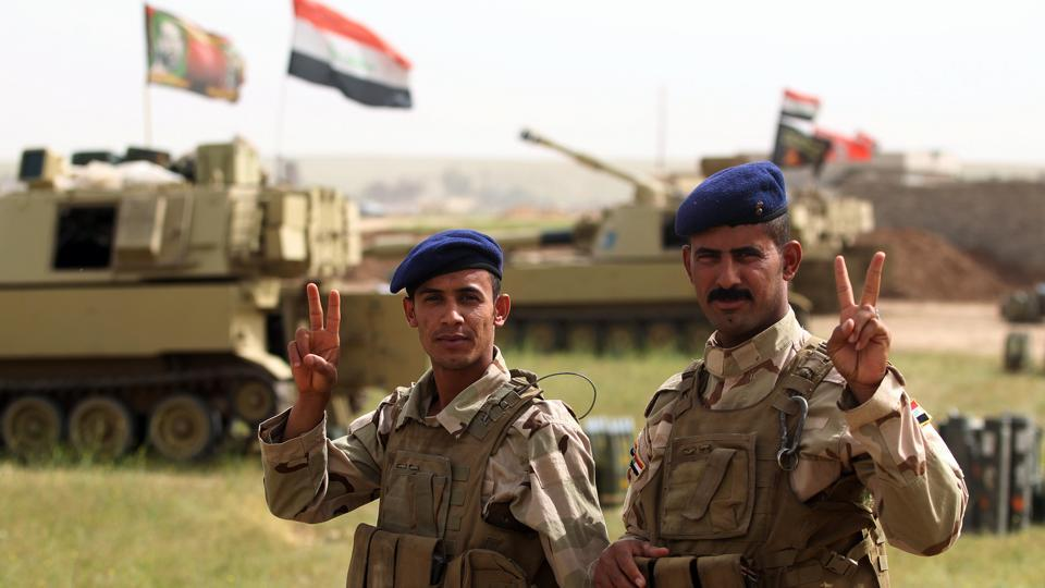 Iraqi soldiers gesture on the frontline in the village of Huleileh, north of Mosul on May 1, 2017, during an offensive to retake the area from Islamic State (IS) group fighters.