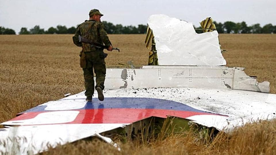 An armed pro-Russian separatist stands on part of the wreckage of the Malaysia Airlines Boeing 777 plane after it crashed near the settlement of Grabovo in the Donetsk region, in this July 17, 2014 file picture.