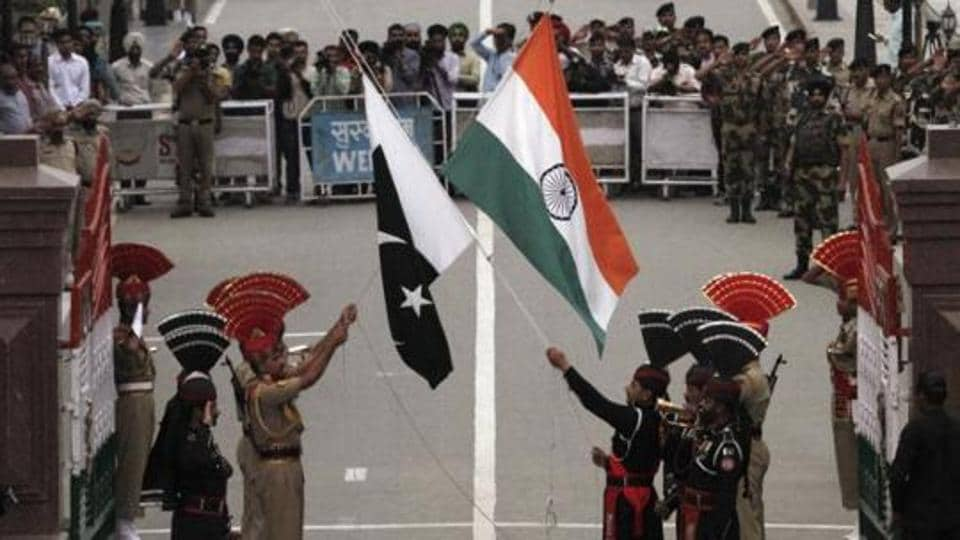 Border Security Force officers and Pakistani rangers lower their national flags during a daily parade at the Wagah border.