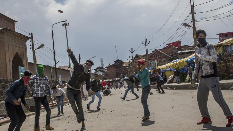 Masked Kashmiri protesters throw rocks and bricks at security forces during a protest in Srinagar.
