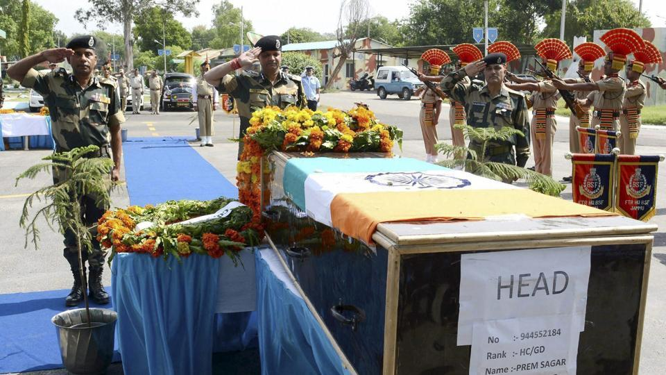 Assistant director general of Border Security Force's Western Command Kamal Nayan Choubey (C) pays his respects to head constable Prem Sagar during a wreath laying ceremony in Jammu on Tuesday.