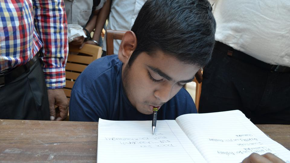 Tuhin Dey holds a pen in his mouth while taking notes at an engineering entrance coaching institute in Kota.