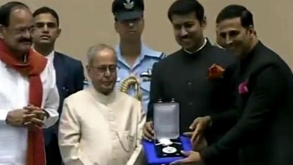 Actor Akshay Kumar receives his National Film Award from President of India Pranab Mukherjee. Standing between Akshay Kumar and Pranab Mukherjee is Rajyavardhan Singh Rathore, minister of state for information & broadcasting.