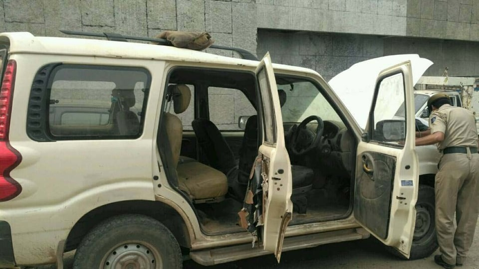 A police official investigating the abandoned SUV in Pathankot on Tuesday.