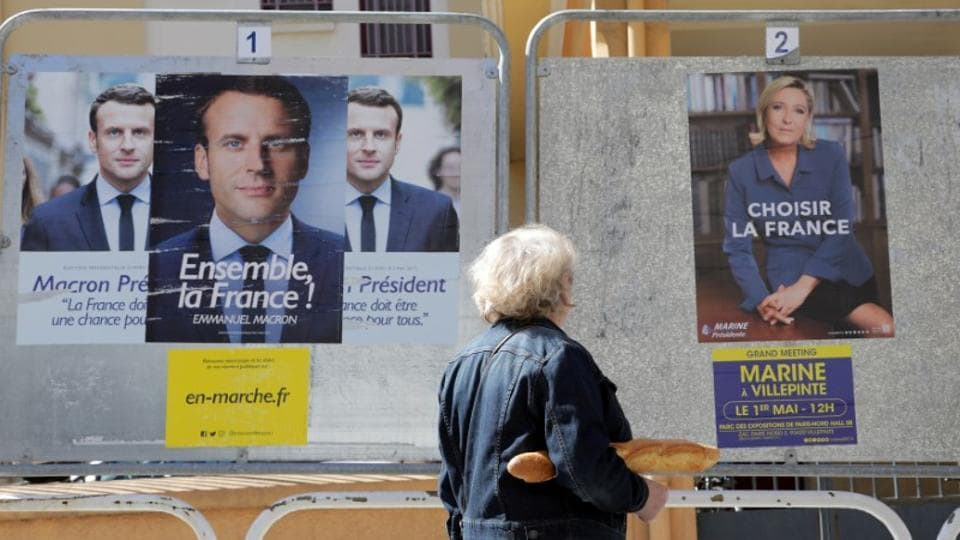 A woman walks past new official posters for the candidates in the 2017 French presidential election, Emmanuel Macron (L), head of the political movement En Marche !, or Onwards !, and Marine Le Pen (R) of French National Front (FN) political party, in Nice, France, May 2, 2017. REUTERS/Eric Gaillard/Files